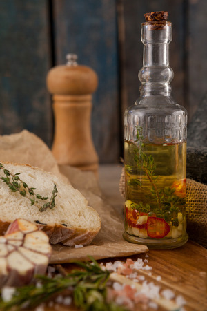 single word: Close up of herb in jar by bread and spices on table