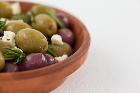 Cropped image of olives with cheese served in bowl on table