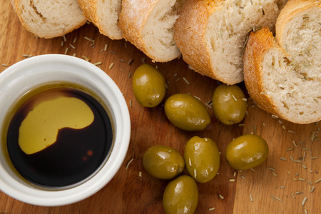 single word: Close up of olives with bread and oil in container on cutting board
