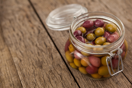 Close up of olives with oil in glass jar on wooden table