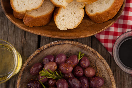 Overhead view of olives and bread with oil in container on table