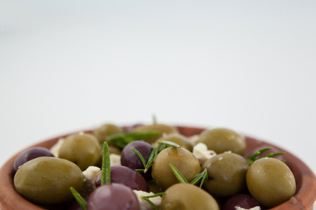 Close up of olives with herb and cheese served in bowl against wall
