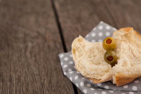 Close up of olives with bread on napkin at wooden table