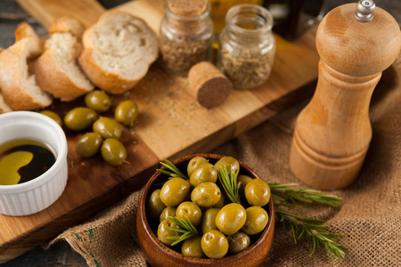 High angle view of olives by pepper shaker and cutting board on table