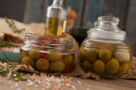 Close up of green olive in glass jars with ingredients on table Stock Photo