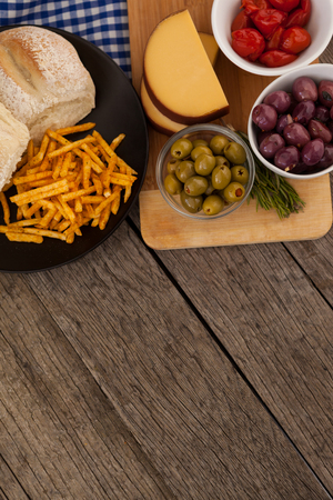 single word: Overhead view of olives with vegetable and french fries in plate on table Stock Photo