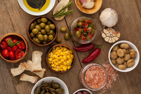 single word: Overhead view of Olives with vegetable and spice by oil in bowl on table