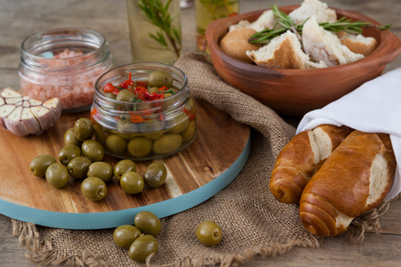 Green olives with containers on cutting board by bread at table