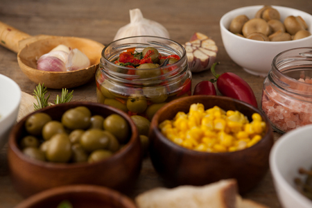 single word: Olives and corns in bowl by spices on table Stock Photo