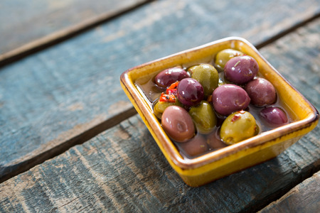 Pickled olives in bowl on wooden table Stock Photo