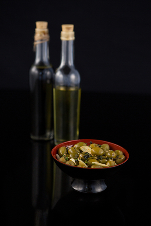 Close-up of marinated olives with olive oil and balsamic vinegar bottle against black background