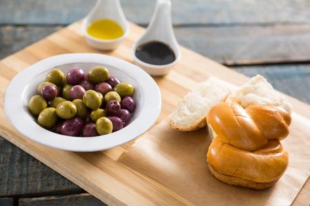 encurtidos: Aceitunas marinadas con pan y aceite de oliva en la tabla de cortar