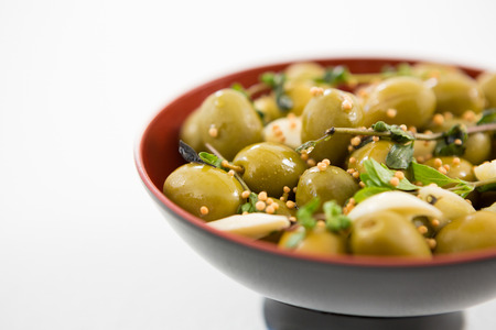 Close-up of marinated olives with garlic and herbs in bowl