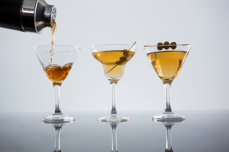 Close-up of cocktail poured in glass with olives on table against white background