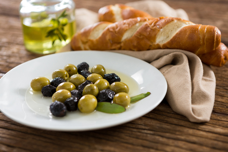 encurtidos: Primer plano de aceitunas marinadas con aceite de oliva y desayuno en la mesa de madera