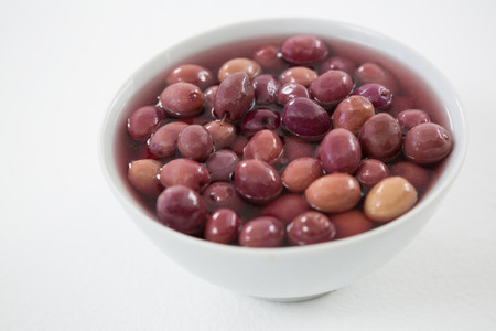 Close-up marinated olives in bowl against white background