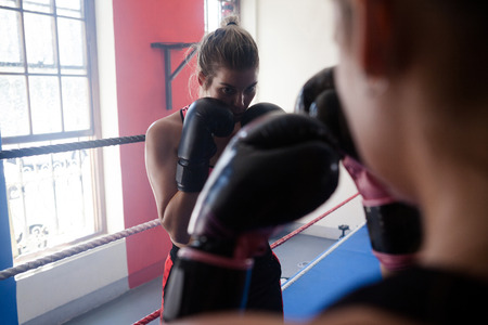 Trainer assisting woman in boxing at fitness studio Stock Photo