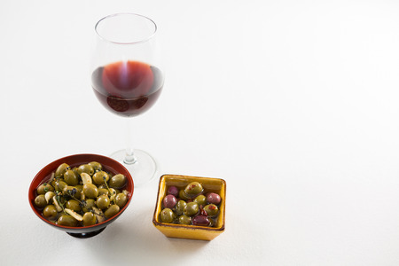 Close-up of marinated olives with glass of wine on white background Stok Fotoğraf
