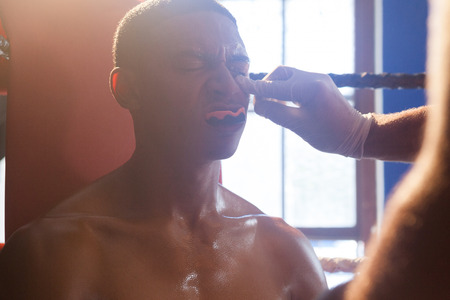 athleticism: Trainer applying cream on man face in boxing ring