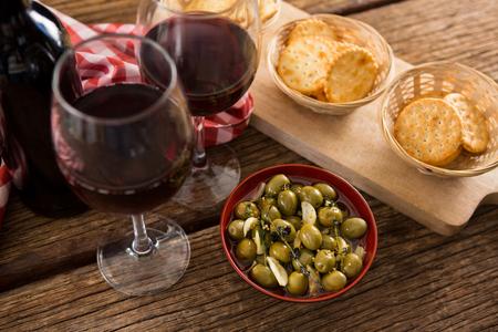 テーブルの上にワインのグラスとオリーブのマリネのクローズ アップ 写真素材