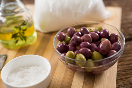 Marinated olives in bowl on wooden table