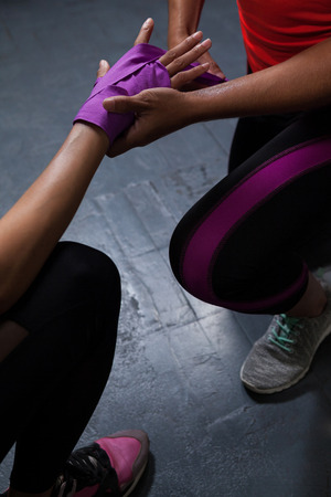 athleticism: Trainer tying hand wrap on woman hand in fitness studio