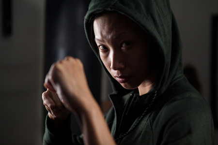Portrait of determined woman practicing boxing in fitness studio