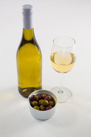 Close-up of marinated olives with glass and bottle of wine on white background Stok Fotoğraf