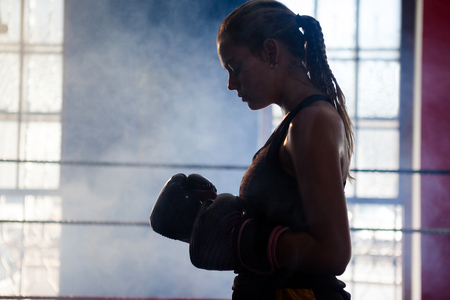 Determined woman standing in boxing ring in fitness studio Stock Photo