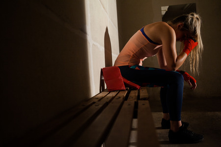 athleticism: Sad woman sitting on bench in fitness studio