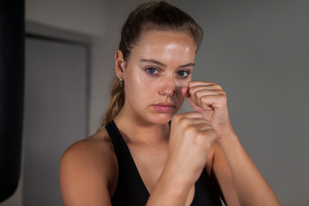Portrait of female boxer practicing boxing in fitness studio