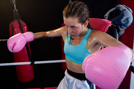 Young female boxer sitting in corner of boxing ring at fitness studio Stock Photo