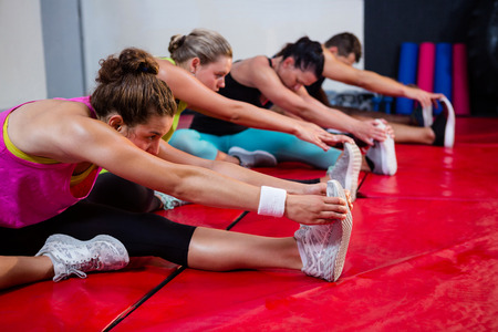 Row of young athletes practicing stretch exercise on mats at fitness studio
