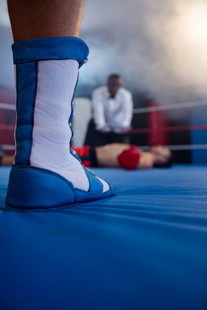 low section: Low section of boxer standing against referee by athlete lying in boxing ring Stock Photo