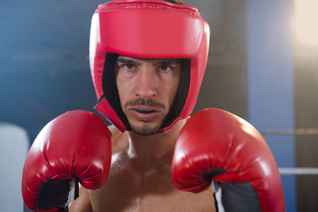 Close-up portrait of confident male boxer wearing red headgear and gloves in boxing ring Stock Photo