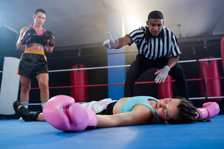 Female boxer looking while referee counting by athlete in boxing ring Foto de archivo