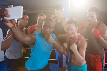 Young boxers taking selfie in fighting stance standing at fitness studio Stock Photo