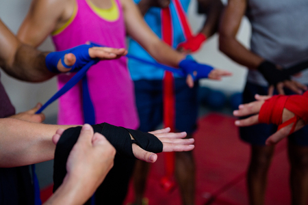 Boxers wrapping bandages on hands in fitness studio