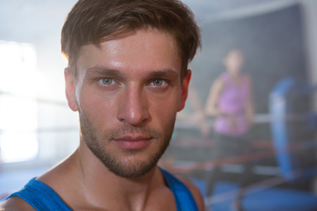 Close-up portrait of young male athlete standing at fitness studio Stock Photo