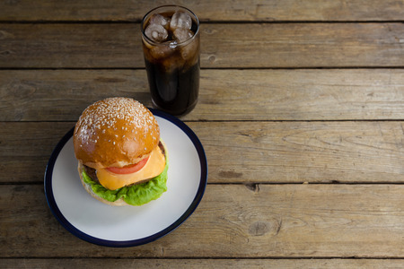 icecubes: Overhead of hamburger in plate with glass of cold drink Stock Photo