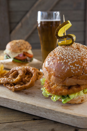 toothpick: Hamburger and onion ring with glass of beer on wooden table