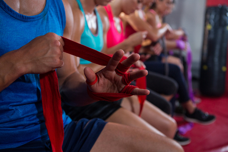 Close-up of athletes wrapping bandages at fitness studio 스톡 콘텐츠