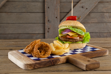 toothpick: Close-up of hamburger, onion ring and french fries on chopping board