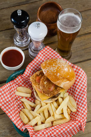 Burger and french fries in wicker basket on wooden table