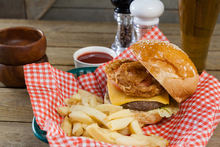 napkin ring: Burger and french fries in wicker basket on wooden table