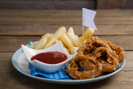 napkin ring: Onion ring and french fries with ketchup arranged in plate on wooden table Stock Photo