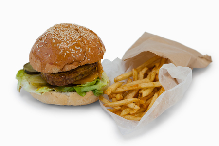 french way: Close-up of hamburger and french fries in take way bag on white background