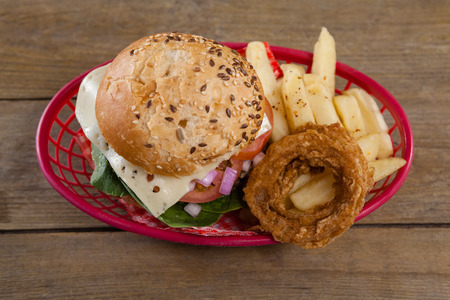 Hamburger and french fries in basket on wooden table