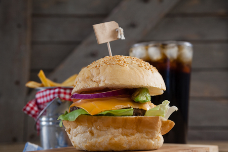 icecubes: Hamburger, french fries and cold drink on table against wooden background