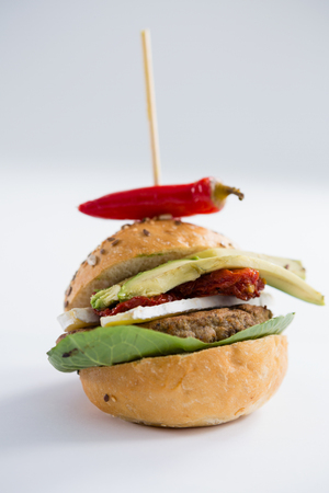 Close up of burger with jalapeno pepper at table